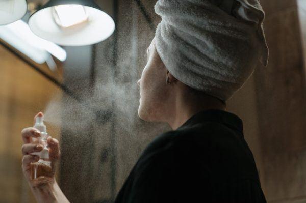 Mujer echa spray en su cutis